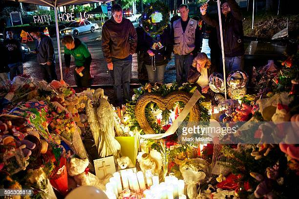 Community members gather to admire a growing memorial to Sandy Hook Elementary School victims on December 18 in Shady Hook CT 4 days after a mass...