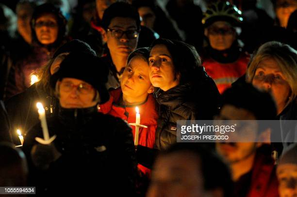 TOPSHOT Community members hold candles at a vigil for the victims of the Pittsburgh Synagogue shooting at Cambridge City Hall in Cambridge...