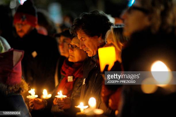 Community members hold candles at a vigil for the victims of the Pittsburgh Synagogue shooting at Cambridge City Hall in Cambridge Massachusetts on...