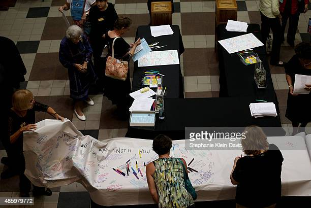 Community members sign a large roll of paper with words and prayers for the families of Alison Parker and Adam Ward following the Interfaith Service...