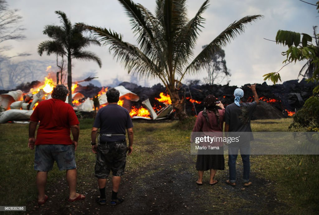 Community members watch as a home is destroyed by lava from a Kilauea volcano fissure in Leilani Estates, on Hawaii's Big Island, on May 25, 2018 in Pahoa, Hawaii. Following a magnitude 4.4 earthquake today centered in the summit region of the Kilauea volcano, an ash plume was sent from the volcano at least 10,000 feet skyward, according to the National Weather Service.