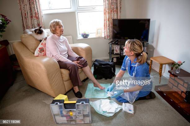 community nurse makes a house call - old lady feet stock pictures, royalty-free photos & images
