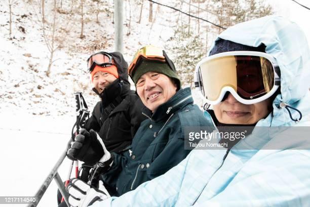a community of seniors riding the ski lift - スポーツ  ストックフォトと画像