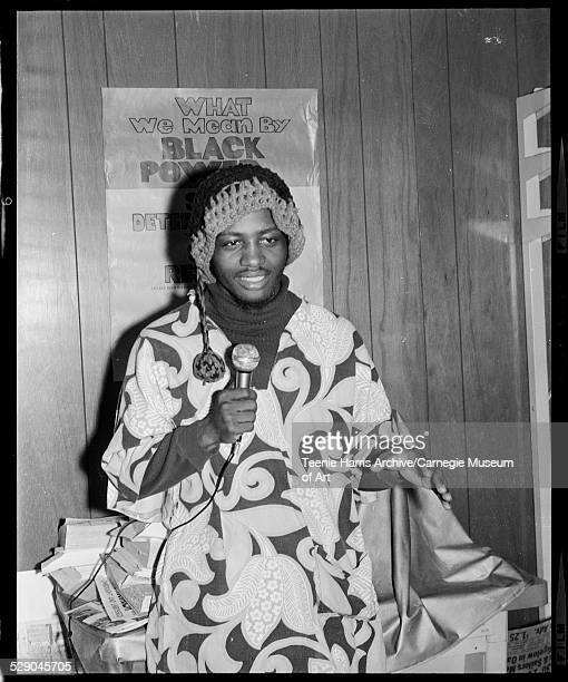 Community organizer Melvin Love wearing dashiki and crocheted hat speaking into microphone in front of poster reading 'What We Mean by Black' in...