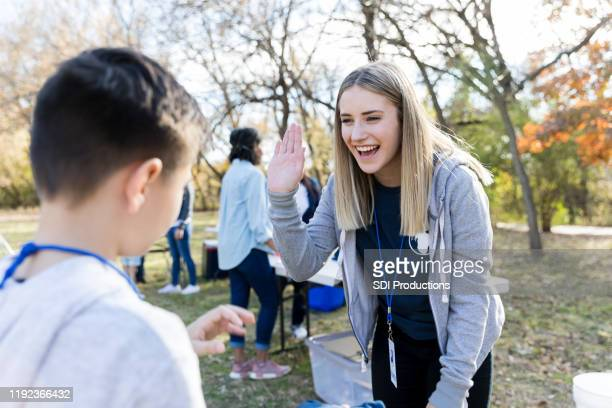 community outreach volunteer coordinator greets young volunteer - charity and relief work stock pictures, royalty-free photos & images