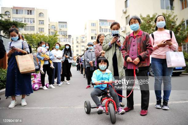 Community residents queued up for nucleic acid testing. Qingdao, Shandong Province, China, October 13, 2020.- PHOTOGRAPH BY Costfoto / Barcroft...