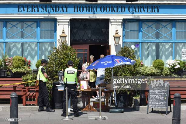 Community Safety officers speak to a woman selling food and drinks outside the entrance of a pub as crowds of people gather on the beach on a warm...