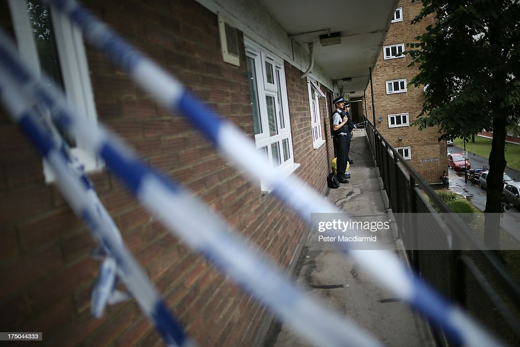 Community support officers stand guard at an address in Elstead House where police are investigating a stabbing incident on July 30, 2013 in Brixton, London, England. Police have detained a 40 year old man after one woman was found dead and two others were stabbed in south London.