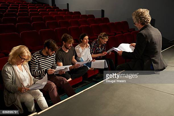 Community theatre group sit and read script.