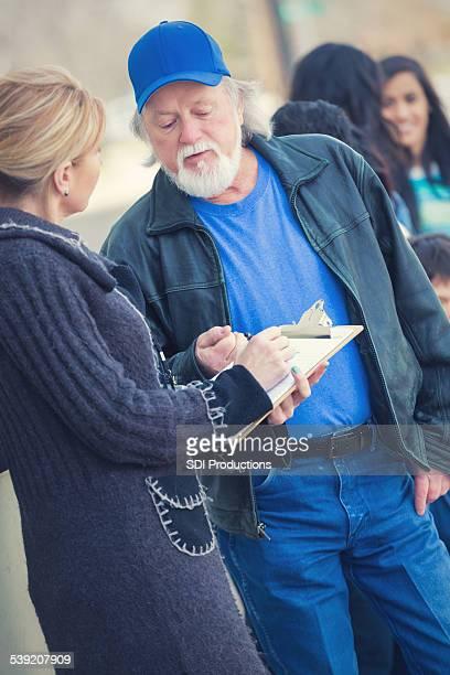 Community volunteer assisting homeless people outside food bank