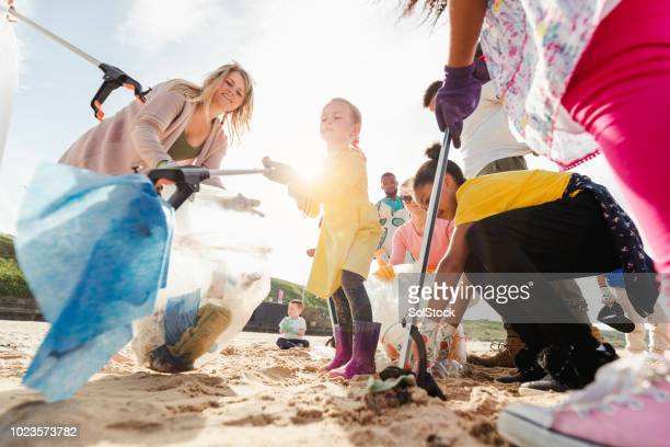 community volunteer groups on the beach - picking up stock photos and pictures