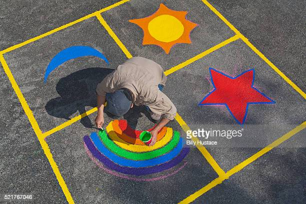 Community volunteer painting a colorful mural on pavement.