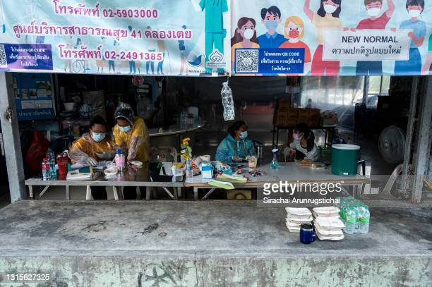 Community volunteers from Khlong Toei slum take seats at the entrance of a village hall converted as a temporary isolation area for Covid-19 patients...