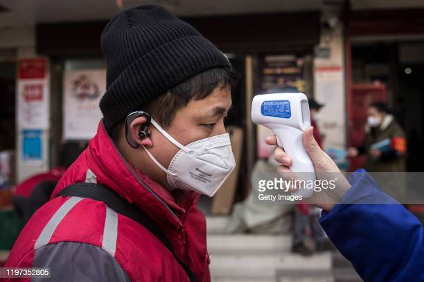 Community worker checks the temperature of courier in an Express station on January 29, 2020 in Hubei Province, Wuhan, China. Due to a transit shut...