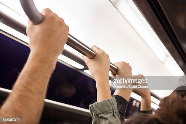 Communters on subway holding grab handle, close-up