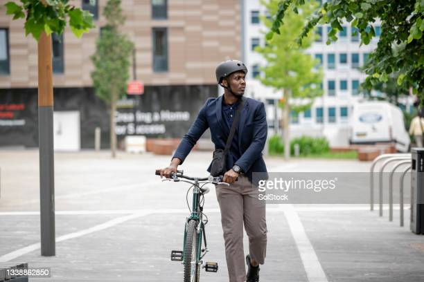 commuter arriving at work with his bicycle - green blazer stock pictures, royalty-free photos & images
