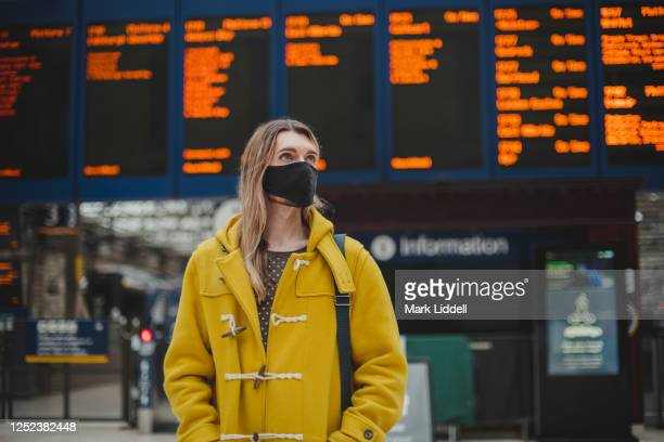 commuter at train station wearing ppe face mask for safety - scotland stock pictures, royalty-free photos & images