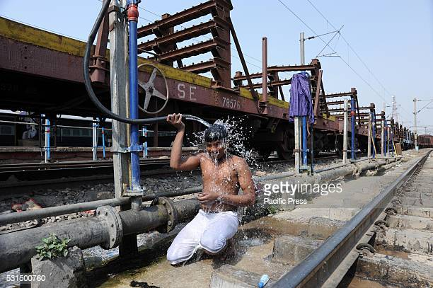 A commuter baths to cool off at Allahabad railway junction during a hot day Much of India is reeling from a heat wave and severe drought conditions...