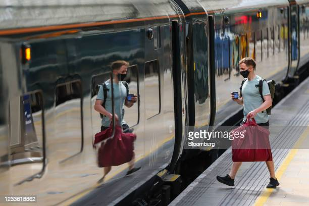 Commuter boards a Great Western Railway train, operated by FirstGroup Plc, at London Paddington railway station in London, U.K., on Monday, July 5,...