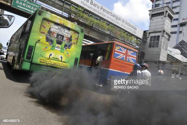 A commuter bus running on diesel fuel emits thick trail of pollutants in Jakarta on December 7 2009 Current pledges from rich and developing nations...