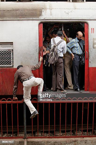 A commuter climbs a fence from the other side of the track to board a train in Mumbai India on Monday Feb 22 2010 Railways Minister Mamata Banerjee...
