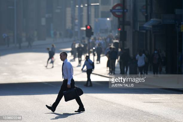 Commuter crosses a road by London Bridge in London on September 15, 2020. - Britain's unemployment rate jumped above four percent in July on economic...