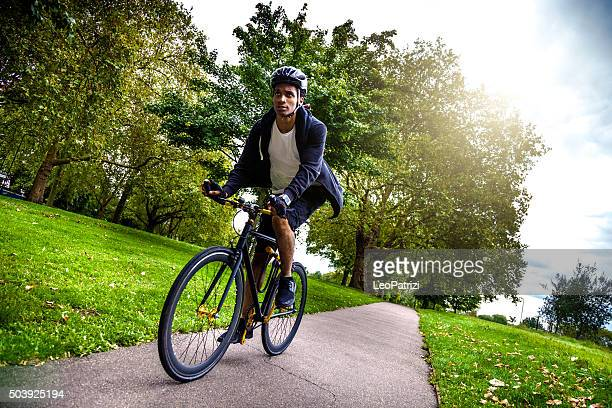 commuter cycling in the park going at work in london - sports helmet stock pictures, royalty-free photos & images
