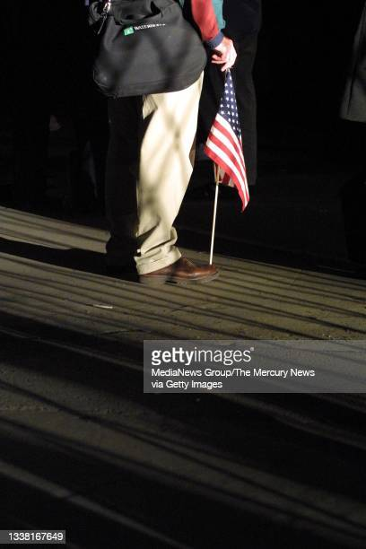 Commuter holds a flag while waiting for a ferry going to Brooklyn from Manhattan on September 17, 2001 in New York. Many New Yorkers returned to work...