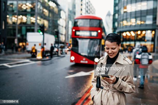 commuter in london using mobile phone while waiting for bus - london stock pictures, royalty-free photos & images