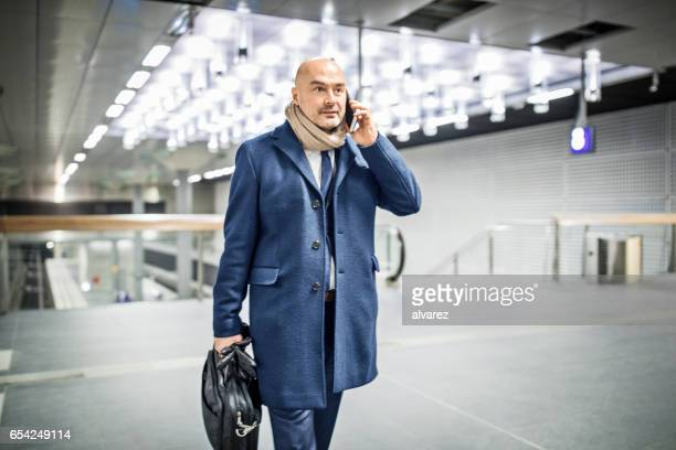 Commuter in subway station talking on mobile phone
