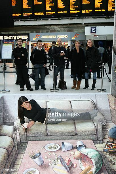 Commuter Katherine Ware relaxes on street artist Kurt Wenner's 3D work of art in Waterloo Station on October 17 2007 in London England The image was...