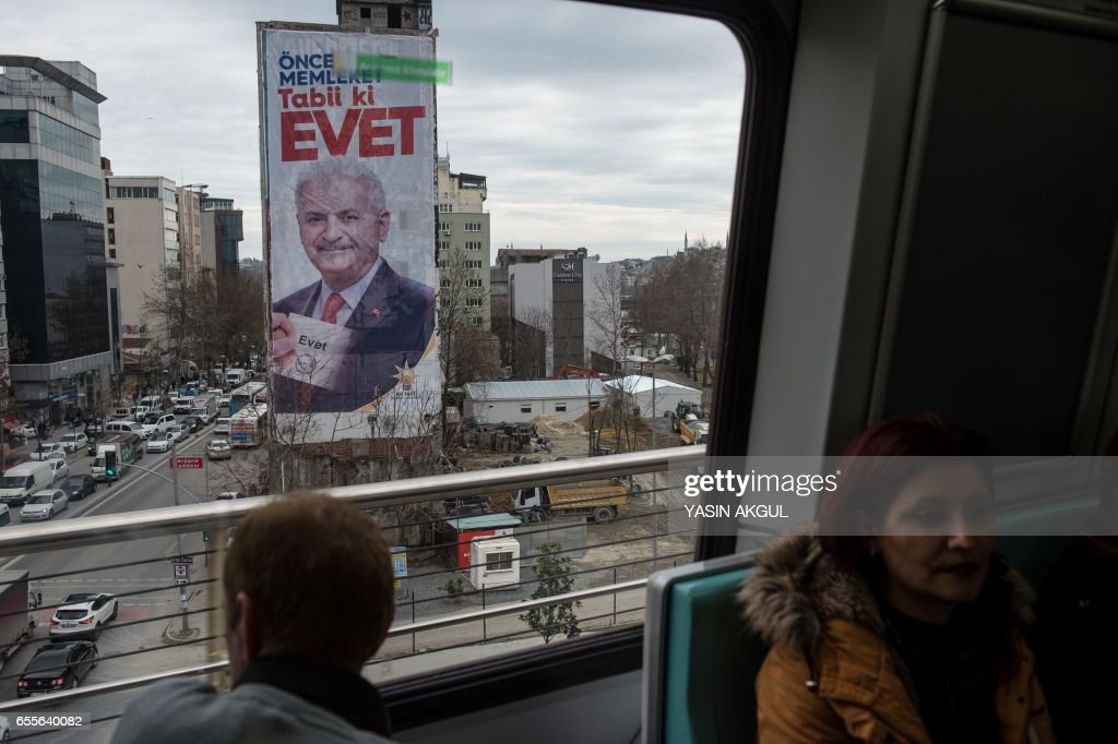 TOPSHOT - A commuter looks at a giant poster of Turkish Prime minister Binali Yildirim on March 20, 2017 in Istanbul. On April 16, 2017, the Turkish public will vote on whether to change the current parliamentary system into an executive presidency. /
