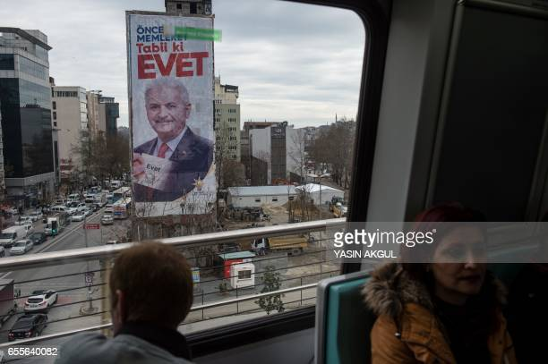 Commuter looks at a giant poster of Turkish Prime minister Binali Yildirim on March 20, 2017 in Istanbul. On April 16 the Turkish public will vote on...