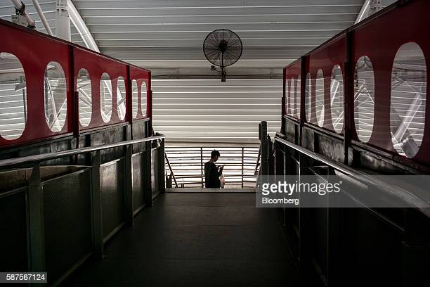 A commuter looks at a mobile phone at the Bukit Bintang station in Kuala Lumpur Malaysia on Friday Aug 5 2016 Malaysia's secondquarter gross domestic...