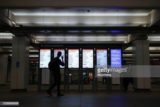 A commuter looks at digital monitors displaying train times at Wynyard railway station in Sydney Australia on Monday July 30 2018 The nation whose...