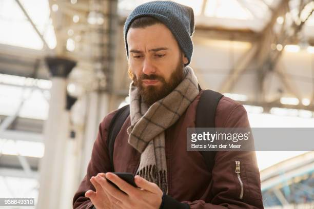 Commuter looks at smartphone while walking in train station.