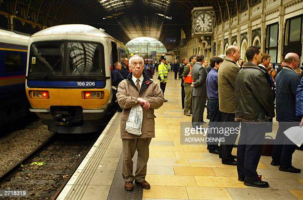 A commuter looks up at a clock to check the time for the beginning of the two minutes of silence to mark Armistice Day at Paddington Station in...