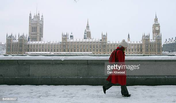 A commuter makes her way past the Houses Of Parliament after a night of heavy snow on February 2 2009 in London England Heavy snow has fallen across...