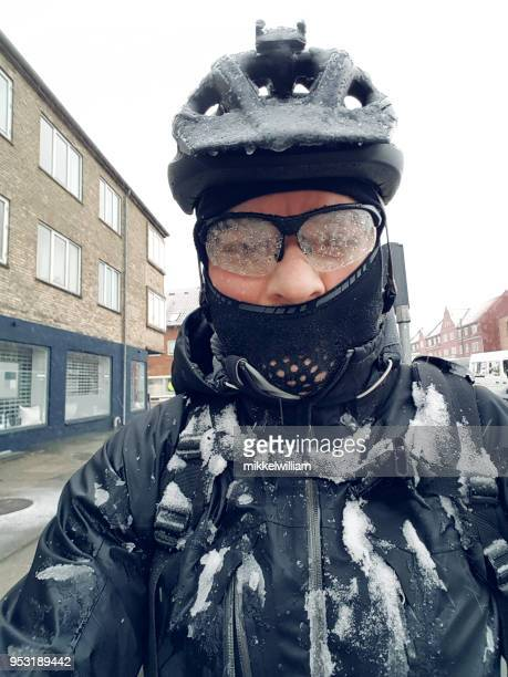 Commuter on bike is covered in snow and ice on the way to work