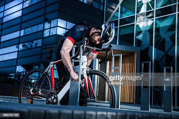 commuter parking his bicycle outside the office entrance - bicycle parking station stock photos and pictures