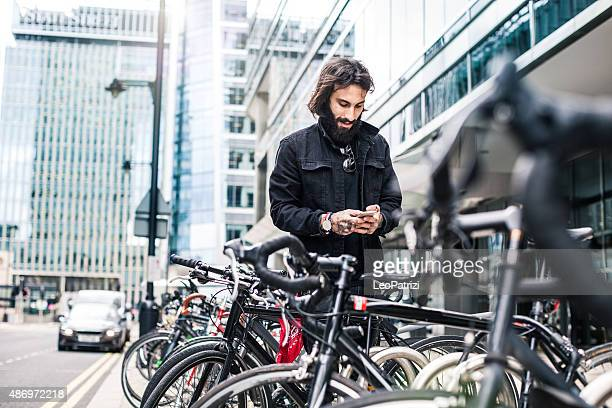 commuter parking his bicycle outside the office - bicycle parking station stock photos and pictures