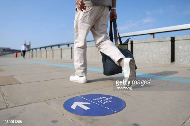 Commuter passes a social distancing sticker while crossing London Bridge, on so-called 'Freedom Day' in London, U.K., on Monday, July 19, 2021. Boris...