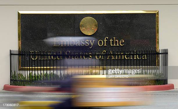 Commuter passes in front of the highly-secured US embassy in Manila on July 6, 2013. The United States issued a warning against travel to the...