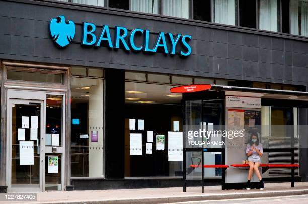 A commuter pedestrian wearing a face mask or covering due to the COVID19 pandemic sits inside a bus shelter by a branch of a Barclays bank in central...