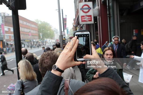 A commuter photographs the bus queue outside Waterloo station London on the second day of a 48 hour strike by tube workers on the London Underground...