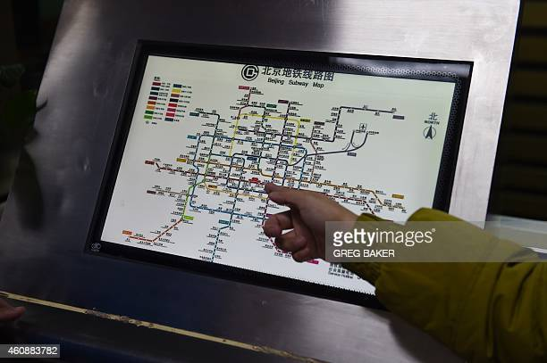 A commuter points at a subway map at a subway station in Beijing on December 29 2014 Beijing on December 28 introduced a new subway fare structure...