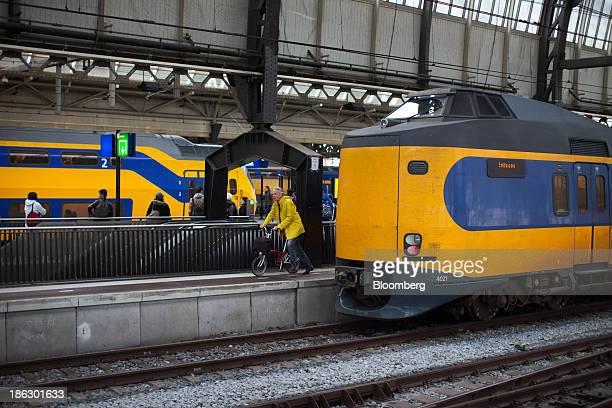 A commuter pushes a bicycle beside a Koploper passenger train operated by Nederlandse Spoorwegen as it sits alongside a platform at Amsterdam...