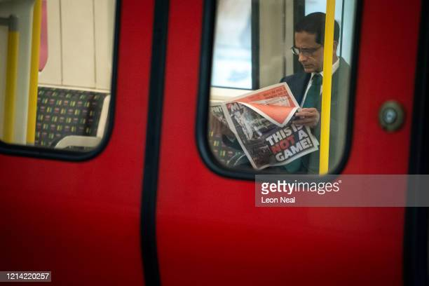 """Commuter reads a newspaper with the headline """"This Is Not A Game!"""" as he travels on an underground train just after 9am, during what would usually be..."""
