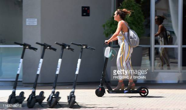 A commuter rides an escooter on the sidewalk in Los Angeles on August 22 where an escooter enforcement task force has been launched in an effort to...