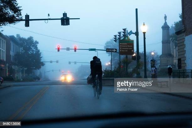 Commuter rides bike on small town square in the early morning